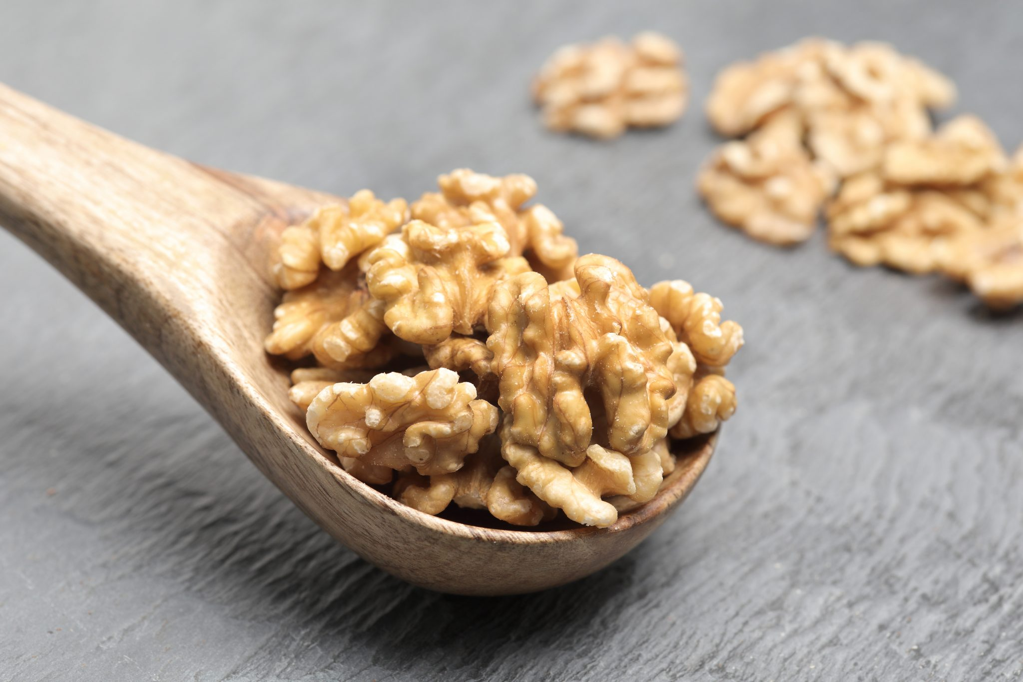 Chandras healthy vegan snack walnut halves on a wooden spoon